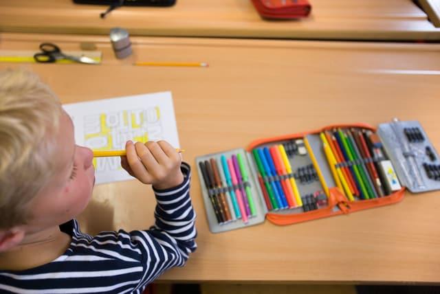 Kind mit Etui und Stiften