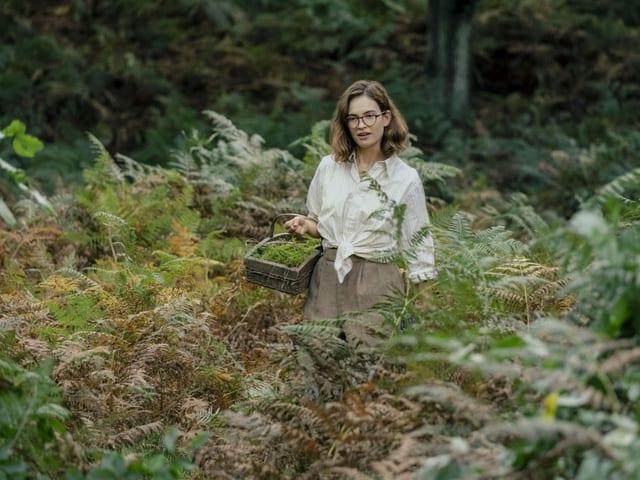 Eine junge Frau läuft durch dichtes Gras. In der Hand hält sie einen Korb, der mit Moos gefüllt ist.