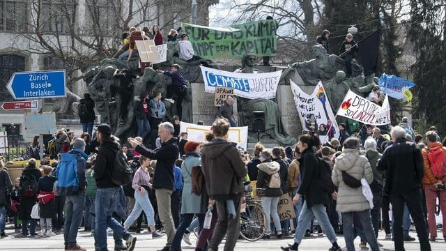 Purtret da persunas che demonstreschan a Berna. Els tegnan si transparents e tavlas cun scrit si diversas parolas.