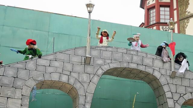 Kostümierte Leute führen auf einer Brücke ein Fasnachtstheater auf.