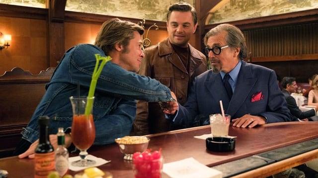 Drei Männer sitzen in einer Bar am Tresen. Zwei von ihnen schütteln die Hand.