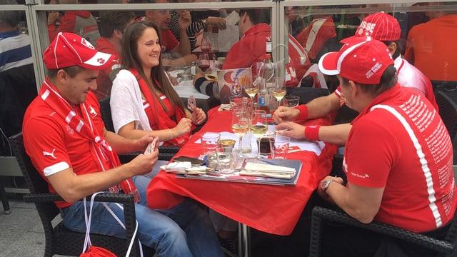 Quatter fans svizzers sesan sin terrassa d'in restaurant a Lille e dattan jass