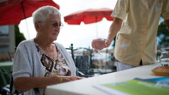 Eine ältere Dame bekommt ein Glas Wasser