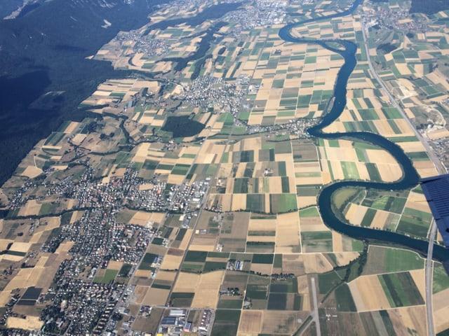 Flugbild mit bewaldeten Hügeln links und Aare rechts im Bild. Dazwischen die trockenen, braunen Felder mit ein paar Dörfern und Städten.