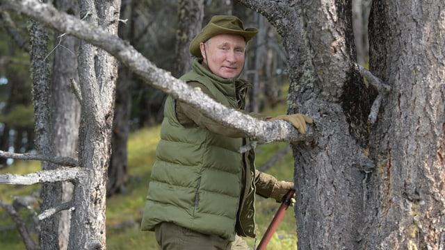Wladimir Putin in der sibirischen Taiga stützt sich an einem Nadelbaum ab.