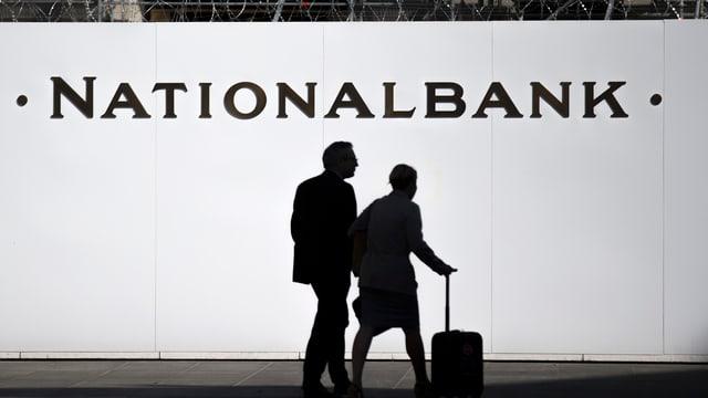 Zwei Personen vor einer Baustellenwand mit der Aufschrift Nationalbank auf dem Berner Bundesplatz
