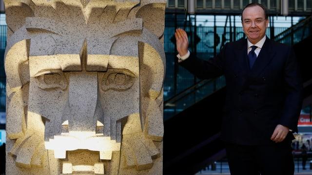 Eine Person steht neben einer Löwen-Skulptur.