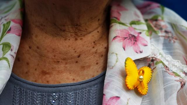 Hals einer Trostfrau, am Revers der geblümten Bluse ein gelber Schmetterlingsanstecker.
