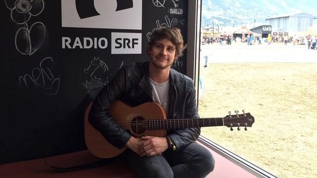 Damian Lynn mit Gitarre und Dreitagebart in der SRF 3-Festivalbox.