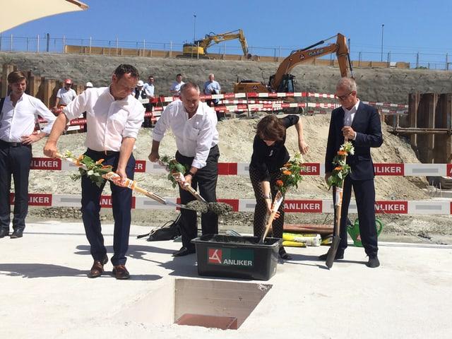 ürg Stöckli (Leiter SBB Immobilien), Hans-Peter Wessels (Baudirektor BS), Barbara Gysi (Programmleiterin SRF 2 Kultur) und Architekt Pierre de Meuron mit Schaufeln in der Hand, dahinter Baustelle.