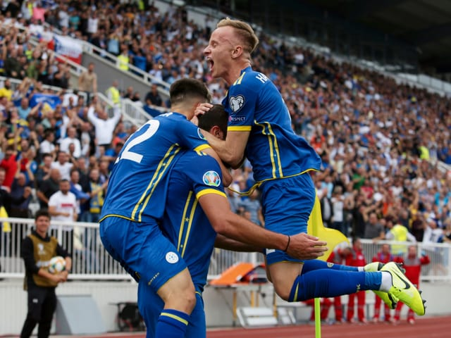 Florent Hadergjonaj springt mit zwei Teamkollegen in die Luft.