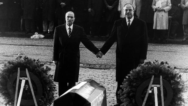 Mitterrand und Kohl halten sich vor Kränzen an der Hand