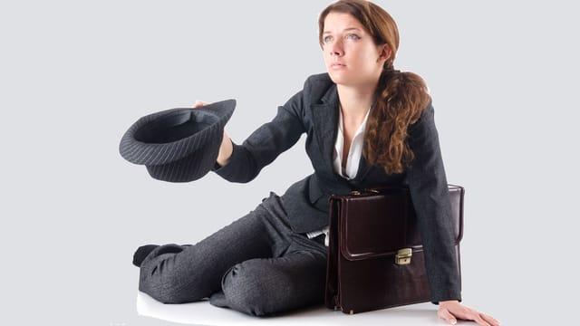 Eine Frau im Business-Outfit sitzt am Boden und bettelt mit einem Hut.