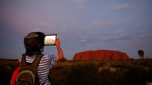 Junge fotografiert den Uluru
