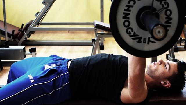 Junger Mann stemmt im Kraftstudio Gewichte