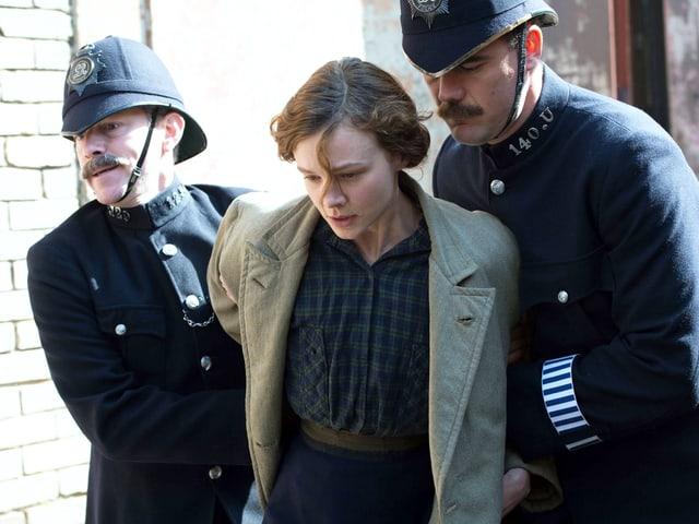 Zwei Polizisten führen eine junge Frau ab.