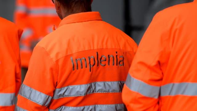 """Mineure von Implenia in roter Arbeitskleidung mit dem Schriftzug """"Implenia"""" auf dem Rücken"""