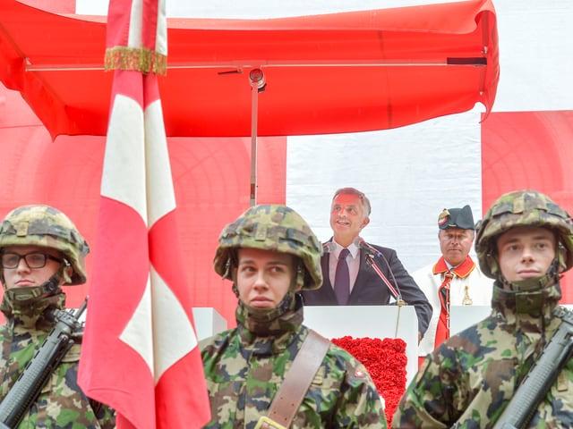Didier Burkhalter am Rednerpult, das mit Schweizer Fahnen verziert ist