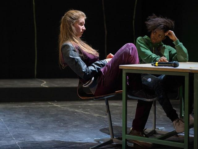 Zwei Mädchen sitzen gelangweilt an einem Schülerpult.