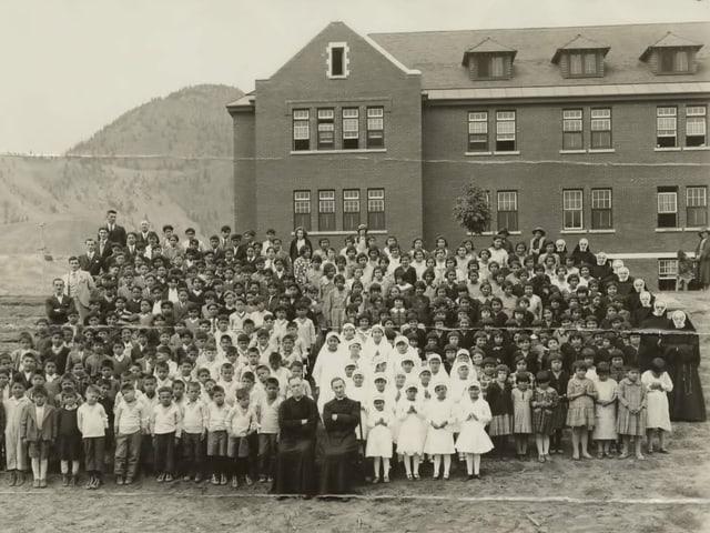 Kinder stehen in Reih und Glied vor einer Schule.