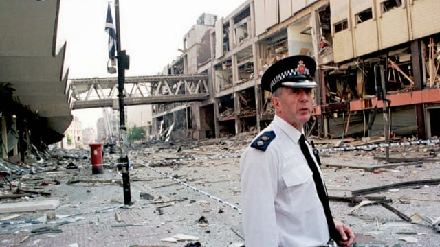 Ein Polizist vor beschädigten Fassaden.