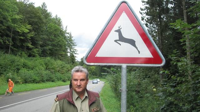 Wildhüter Ruedi Zbinden steht vor einem Verkehrsschild, das einen Wildwechsel anzeigt.