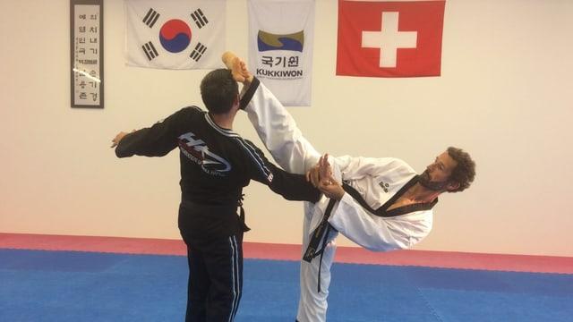 Zwei Akteure betreiben die Kampfsportart Taekwondo