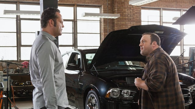 Zwei Männer stehen in einer Garage vor einem Auto mit geöffneter Motorhaube.