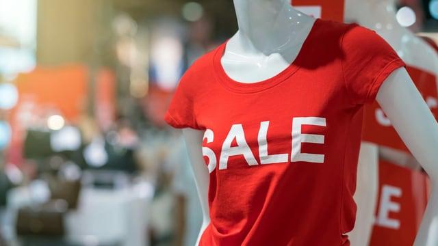 """Eine Schaufensterpuppe trägt ein rotes T-Shirt mit der Aufschrift """"Sale""""."""
