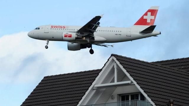 Ein Flugzeug mit Schweizerkreuz auf dem Heck fliegt ganz knapp über das Dach eines Wohnhauses.
