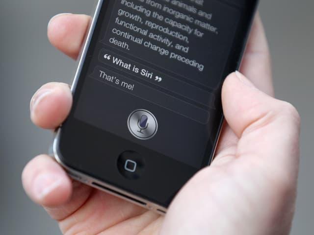 Hand hält iPhone, auf dem Bildschirm ist Siri aufgerufen