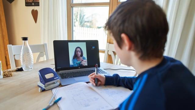 ein junger Bub erhält von seiner Lehrerin am Laptop Instruktionen