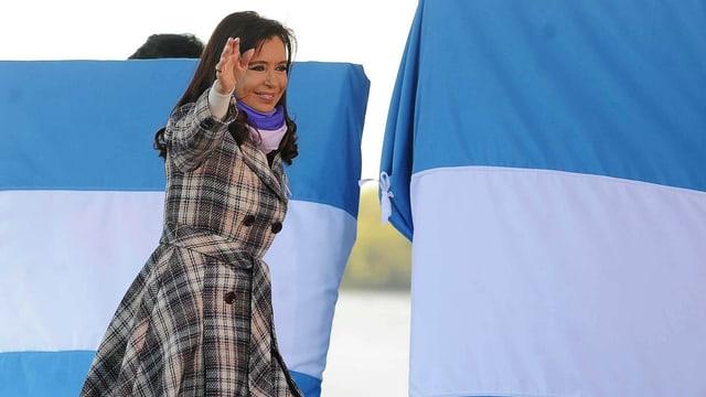 Argentiniens Präsidentin Cristina Fernandez Kirchner winkt, hinter ihr zwei aufgespannte argentinische Fahnen.