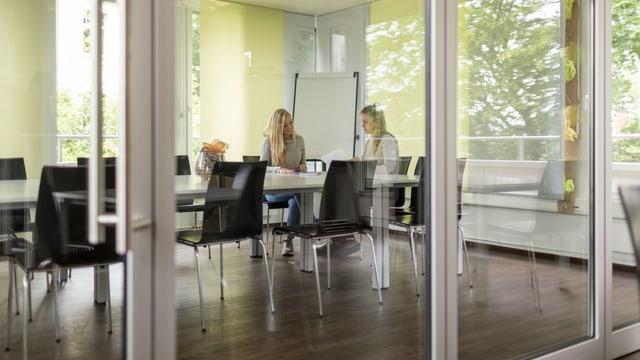 Zwei Frauen sitzen in einer Firma an einem Tisch.