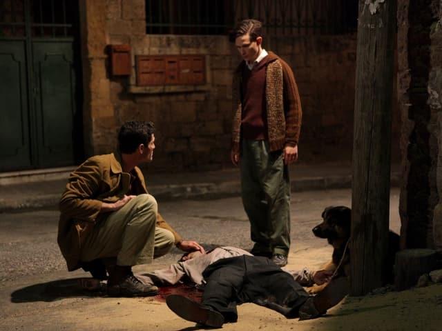 Zwei Männer, einer kniend, der andere stehend, neben einer Leiche.