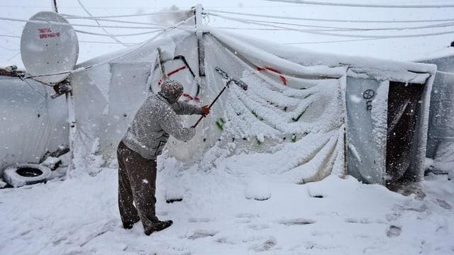 Ein Mann klopft Schnee von seinem Zelt in einem Flüchtlingslager.
