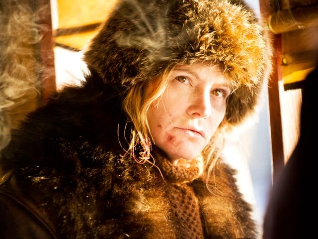 Jennifer Jason Leight dick eingepackt in einer Kutsche.