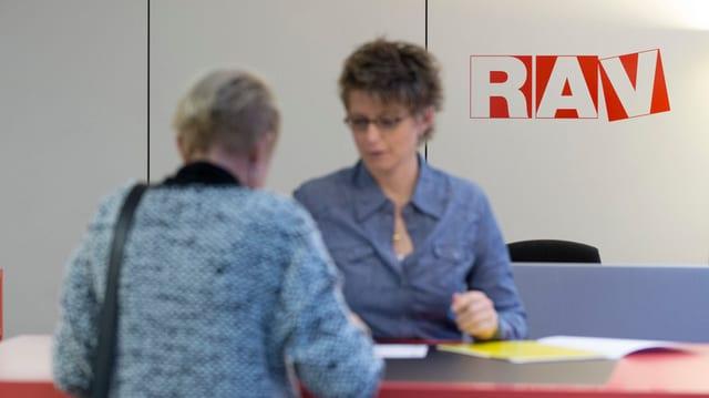 Eine Frau spricht mit einer anderen Frau vor dem Schriftzug RAV