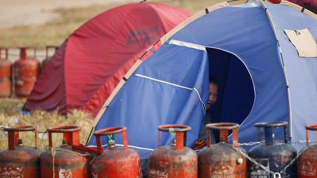 Tendas per abitar a Kathmandu. Davantvi buttiglias da gas per cuschinar vidas.