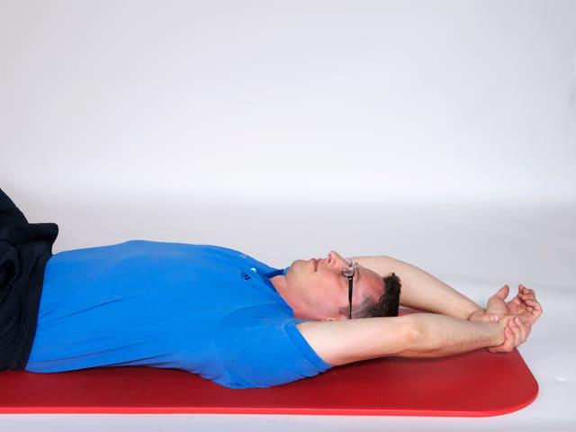 Mann liegt auf Rücken und hat die Arme nachhinten ausgetreckt