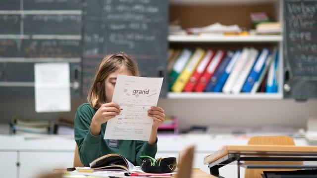 Eine Schülerin sitzt an ihrem Pult und hat ein Blatt vor dem Kopf - sie liest