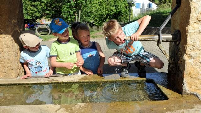 Kinder erfrischen sich am Dorfbrunnen in Bretzwil BL