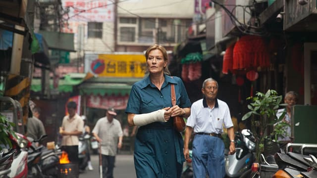 Eine Frau mit bandagiertem Arm geht durch eine Strasse in China.
