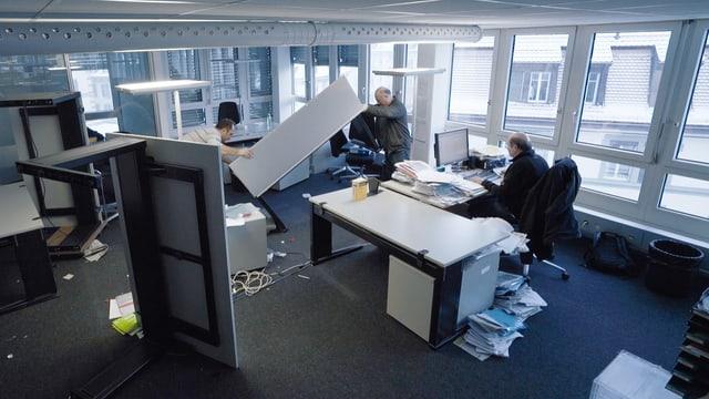 Zwei Mitarbeiter räumen ein Büro.