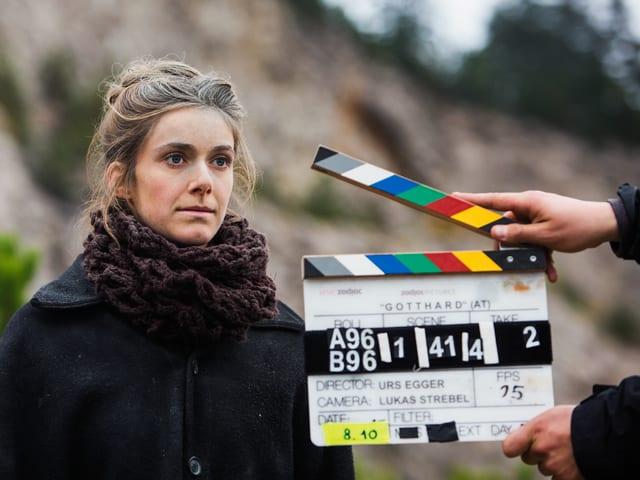 Eine junge Frau in dunklem Mantel steht vor einer geöffneten Filmklappe, die jemand ins Bild hält.