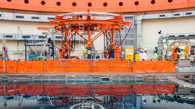 Reaktor, Orange Maschine, einige Leute drumherum.