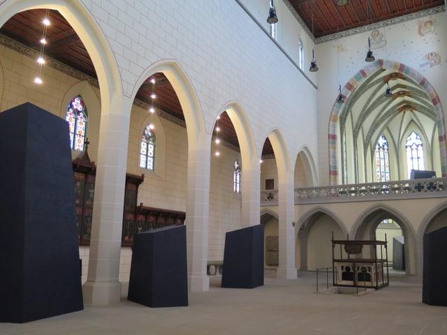 Blaue Holzobjetkte in einer Kirche.