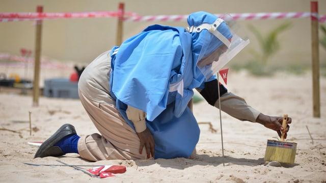 Eine Person beim Entschärfen einer Landmine.