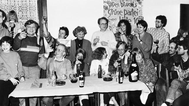 Eine Gruppe von fröhlichen Menschen sitzen dund stehend an einem Tisch, hinten ein Grünen-Transparent