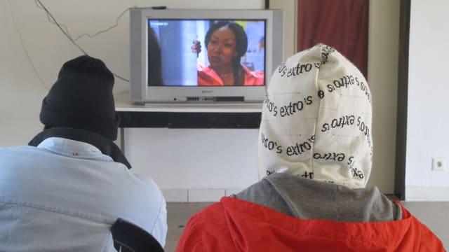 Zwei Asylbewerber sitzen vor einem Fernseher.